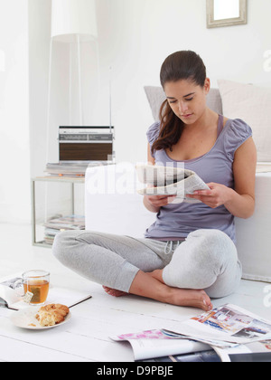 Bruna giovane donna quotidiano di lettura a casa Immagini Stock