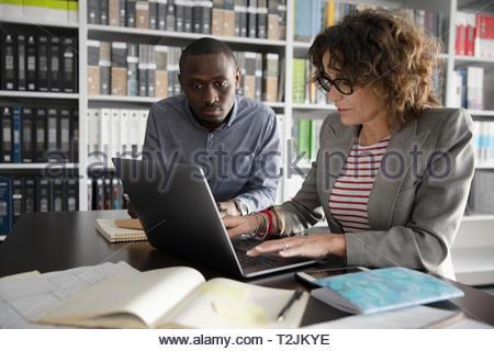 Interior designer che lavorano al computer portatile in design studio Immagini Stock