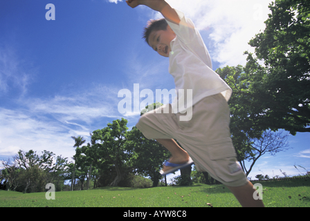 Boy jumping nel parco Immagini Stock