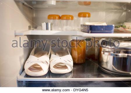 Scarpe in piedi in un frigorifero tra negozi di generi alimentari Immagini Stock