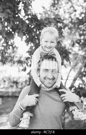 Padre che porta il suo figlio piggyback Immagini Stock