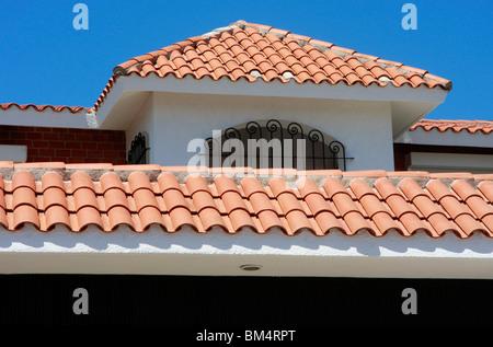 Tipico tetto luminoso tiling su una villa moderna in Mazatlan,Messico,contrasta con un cielo blu brillante Immagini Stock