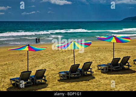 Ombrelloni da spiaggia e stagliano persone che passeggiano lungo la spiaggia di Karon Beach, Phuket, Tailandia Immagini Stock