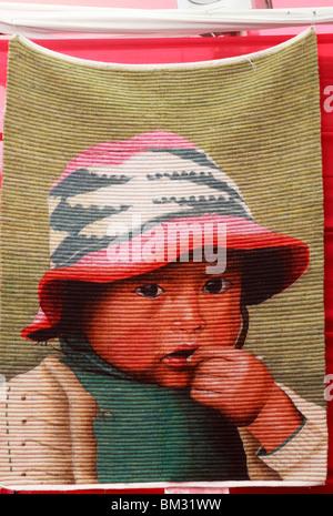 Peruviano appeso a parete,rug,per la vendita turismo negozio di artigianato, Lima, dotate di Andes bambino in hat Immagini Stock