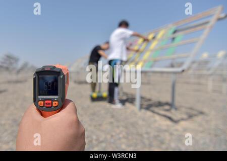 """(190717) -- TURPAN, luglio 17, 2019 (Xinhua) -- ricercatori effettuare un controllo di routine su esperimento i campioni sotto la diretta esposizione alla luce solare al Xinjiang Turpan Ambiente Naturale Experimental Research Center di Turpan, a nord-ovest della Cina di Xinjiang Uygur Regione autonoma, 17 luglio 2019. Un termometro elettrico adottate per l'esperimento sito legge 69,1 gradi Celsius. Conosciuta come """"la terra di fuoco"""" con la sua estremamente caldo e il clima è secco, Turpan nel nord ovest della Cina è diventata una delle scelte migliori per il mondo società automobilistica, materiale i fabbricanti e gli istituti di ricerca che cercano un experim Immagini Stock"""