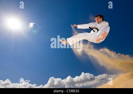 La cintura nera di arti marziali in attacco di volo. Immagini Stock