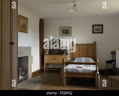 Il servo la camera con un letto in legno e armadio al posto letto e una radio a Castle Drogo, Devon. Immagini Stock