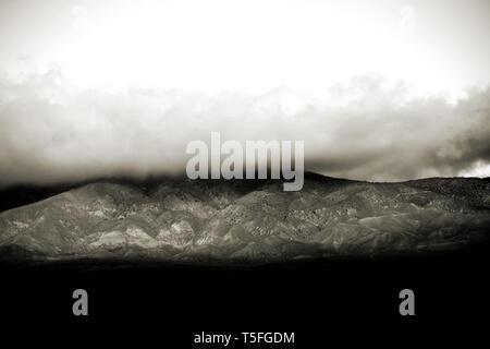Le nuvole e la nebbia tirare sulle cime e creste di una montagna o una catena montuosa. Immagini Stock