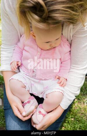 Close up Caucasian baby ragazza seduta in grembo di madre Immagini Stock