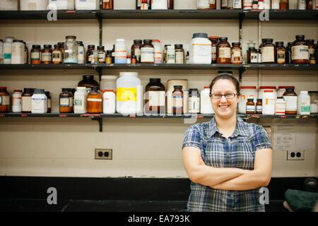 Ritratto di sorridere a metà donna adulta contro la parete montati ripiani con bottiglie da laboratorio Immagini Stock