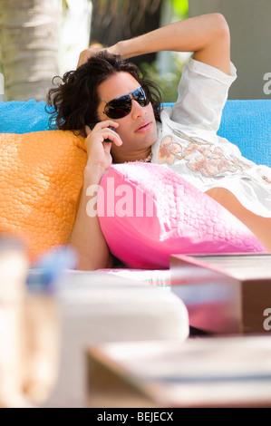 Giovane uomo sdraiato su un lettino e parlando al telefono cellulare Immagini Stock