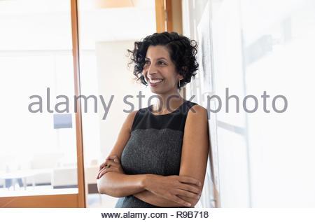 Ritratto fiducioso, imprenditrice sorridente in ufficio Immagini Stock
