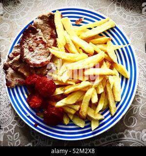 Patate fritte, salsicce ( ) il chorizo iberico e bistecche di carne in Prado del Rey, Sierra de Cadice, Andalusia, Spagna Immagini Stock