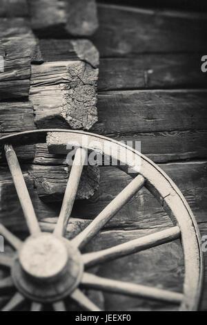 Vecchia ruota del carro al di fuori di edificio rurale parete. In legno rustico oggetto di nostalgia. Immagini Stock