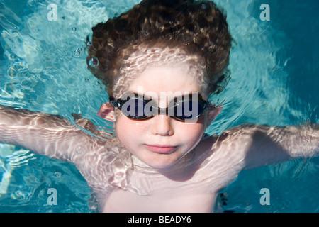 Un giovane ragazzo che indossa gli occhiali di protezione e che galleggia in acqua Immagini Stock