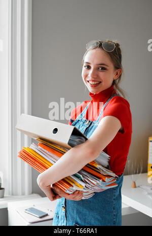 Ritratto fiducioso femmina giovane studente di college che trasportano pila di libri e di legante Immagini Stock
