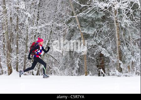 Esecuzione del pareggiatore tramite un inverno nevoso foresta. Immagini Stock
