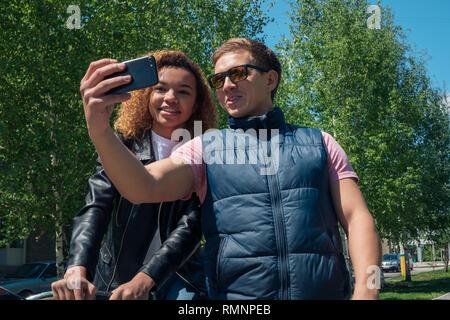 Ragazza africana ed europea di guy tenendo selfie sulla strada Immagini Stock