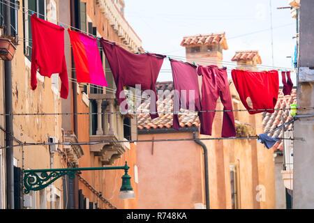Rosso e rosa su capi di abbigliamento stendibiancheria esterno case tradizionali, Venezia, Veneto, Italia Immagini Stock