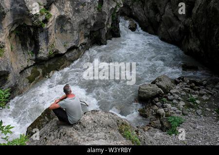 Un escursionista si siede presso la banca di fiume Fiagdon nella Repubblica di Ossezia del nord - Alania nel Nord Caucaso Distretto federale della Russia. Immagini Stock