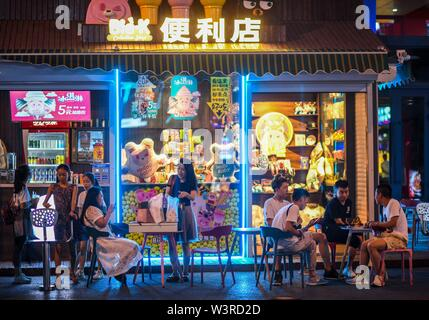 Urumqi, della Cina di Xinjiang Uygur Regione autonoma. 14 Luglio, 2019. Le persone hanno un resto di fronte ad un negozio di Urumqi, a nord-ovest della Cina di Xinjiang Uygur Regione autonoma, luglio 14, 2019. Notte-economia di tempo è stato il prelievo in Urumqi a partire dal mese di luglio. Le persone si divertono a raffreddare le notti estive da shopping e degustazione del cibo. Credito: Zhao Ge/Xinhua/Alamy Live News Immagini Stock
