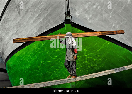 Indonesia, Java, Giacarta, Dock lavoratore a camminare su una tavola con la prua di una nave in background Immagini Stock