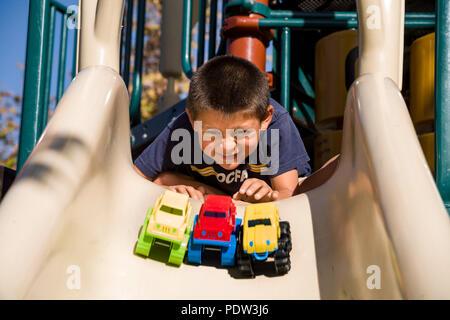 Little Boy felicemente la visione di toy carrello andare giù il parco giochi far scorrere il sig. © Myrleen Pearson ....Ferguson Cate Immagini Stock