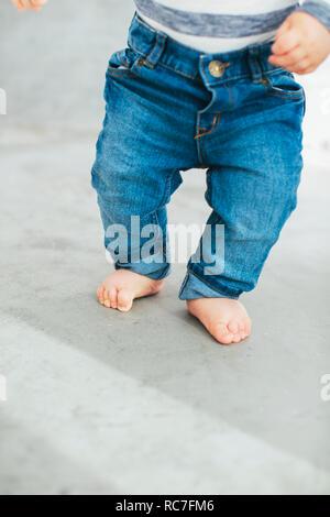 Baby boy cercando di camminare sul pavimento Immagini Stock