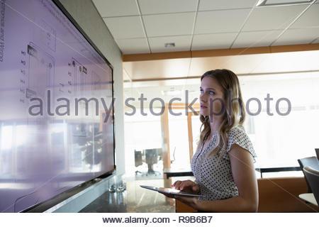 Focalizzato imprenditrice esaminando i piani sullo schermo del televisore in sala conferenze Immagini Stock