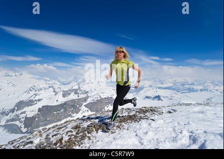 Donna jogging attraverso montagne innevate. Immagini Stock