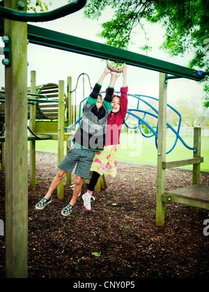 Un ragazzo e una ragazza swing insieme sul telaio di arrampicata. Immagini Stock