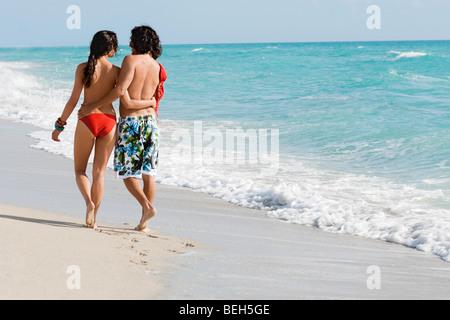 Vista posteriore di una giovane coppia di camminare sulla spiaggia Immagini Stock