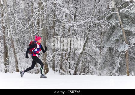 Un pareggiatore in esecuzione attraverso un gelido foresta. Immagini Stock