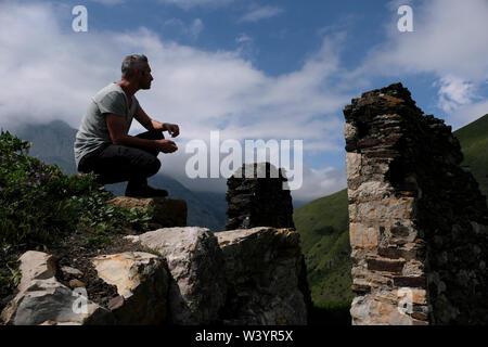 Un escursionista si siede sopra le rovine di Fiagdon borgo montano Kurtatinskoe gorge situato nella Repubblica del Nord Ossetia-Alania nel Nord Caucaso Distretto federale della Russia. Immagini Stock