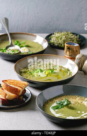 Varietà di verdura verde zuppa di asparagi, broccoli e piselli, decorata da verdi, verdure, uova di quaglia, crema, olio d'oliva, in ciotole di ceramica su grigio Immagini Stock