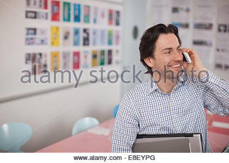 Imprenditore sorridente holding laptop e libri a parlare con il cellulare in ufficio Immagini Stock