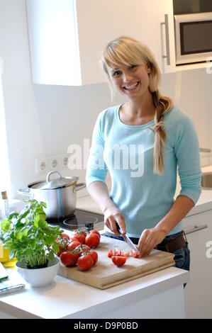 La donna per affettare i pomodori in cucina Immagini Stock