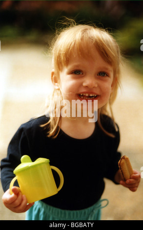 Fotografia della ragazza vivaio bere kids cup non sano fuoriuscite Immagini Stock