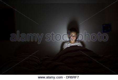 Ragazza con una tavoletta digitale nel letto Immagini Stock