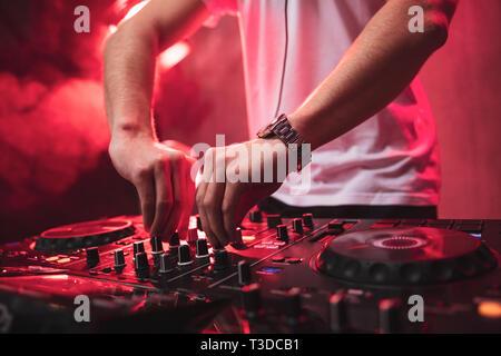 Il mixaggio DJ al party festival con la luce rossa e il fumo in background - Estate vista notturna della discoteca all'interno. Focus sulle mani Immagini Stock