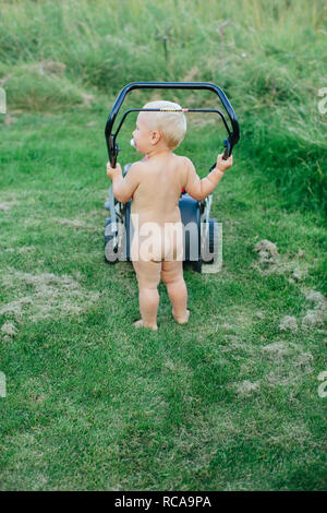 Naked toddler spingendo tosaerba Immagini Stock