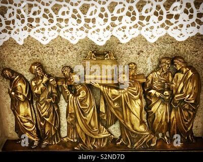 Una scultura dorata di persone che trasportano l'arco dell'Alleanza è visualizzato in una chiesa di Caceres, Estremadura, Spagna Immagini Stock