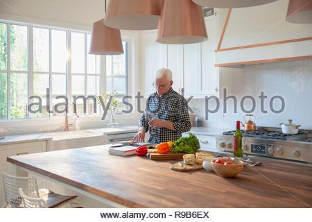 Uomo Senior per la cottura, bere vino e guardando il ricettario di cucina Immagini Stock