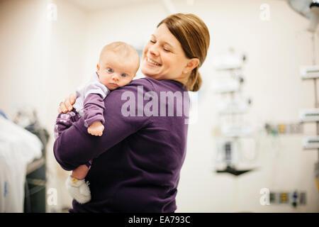 Madre in piedi in ospedale azienda figlio bambino (6-11 mesi) Immagini Stock
