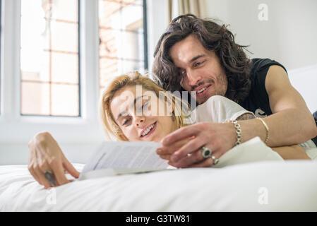 Raffreddare una coppia giovane giacente su un letto guardando un libro. Immagini Stock
