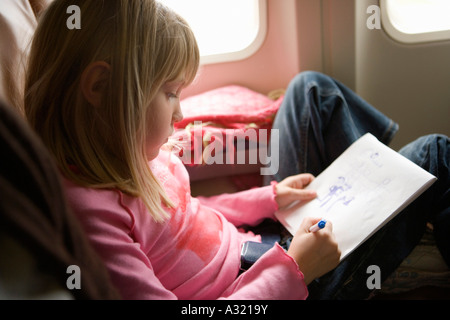 Giovane ragazza seduta in un aereo e disegno in un sketch pad Immagini Stock