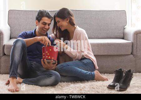 Coppia giovane mangiare popcorn seduto sul pavimento Immagini Stock