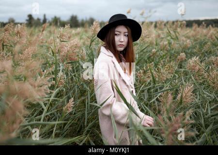 Donna asiatica in piedi in campo Immagini Stock