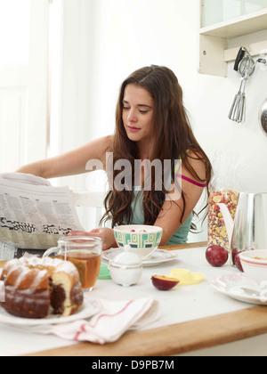 Bruna giovane donna quotidiano di lettura al tavolo per la colazione Immagini Stock