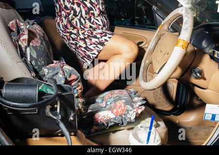 La sezione centrale della donna di entrare in sua automobile. Immagini Stock